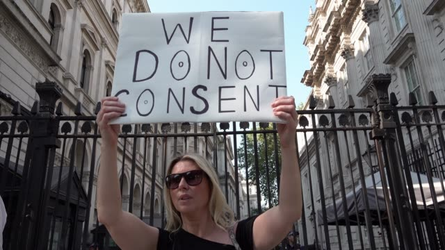 """protestor opposing the rule of six law holds a placard that says """"we do not consent"""" outside downing street in westminster on september 14, 2020 in... - chauffeur stock videos & royalty-free footage"""