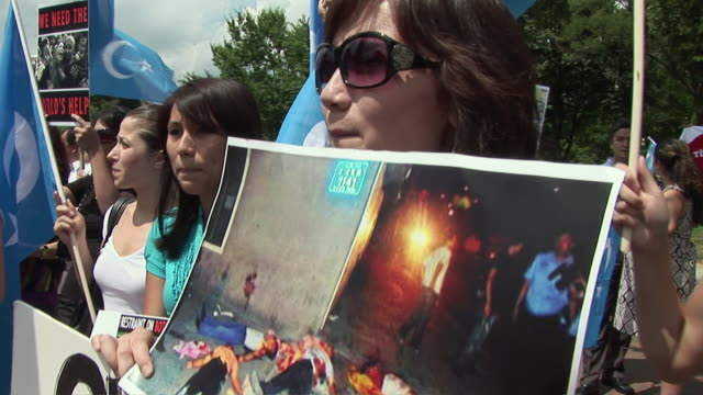 Protestor shouting slogans and holding photograph of violence in China against the Uygur people during an antiChina protest in support of the Uygurs/...