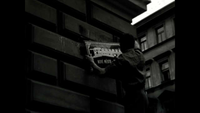 A protestor takes down the street signs to confuse the Soviet invaders at the height of the Prague Spring invasion
