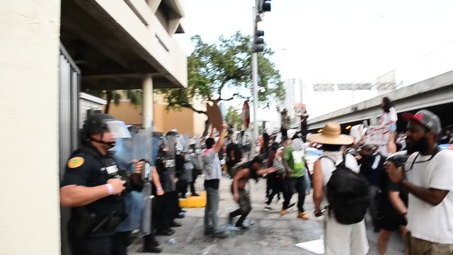 protestors confront miami police officers in riot gear in front of the miami police station as they protest police brutality on may 30, 2020 in... - confrontation stock videos & royalty-free footage