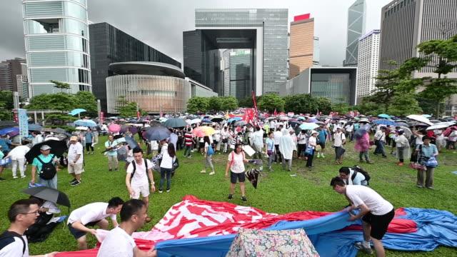 vídeos de stock, filmes e b-roll de protestors gather at tamar park during the progovernment safeguard hong kong rally in hong kong china on saturday july 20 2019 - ilha de hong kong