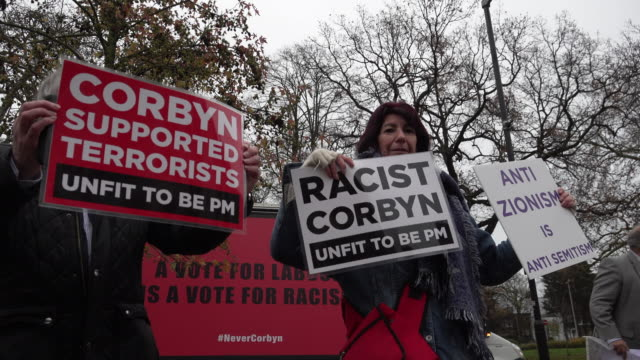 protestors hold placards calling labour leader jeremy corbyn a racist and terrorist supporter outside labour race and faith manifesto launch in... - jeremy corbyn stock videos & royalty-free footage