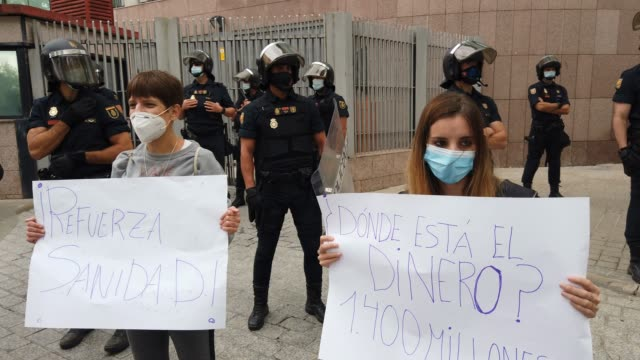 protestors hold signs near police monitoring the area during a demonstration, in the vallecas neighborhood, against the measures imposed by the... - number 2 stock videos & royalty-free footage