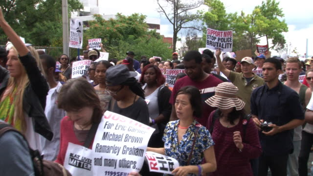 protestors hold signs while walking during the protest / demonstrators march and chant in protest at the we will not go back march for justice march... - police brutality stock videos and b-roll footage