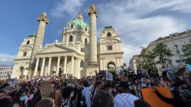 protestors holding signs in front of karlskirche during a black lives matter march on june 04, 2020 in vienna, austria. the death of an... - カールスプラッツ点の映像素材/bロール