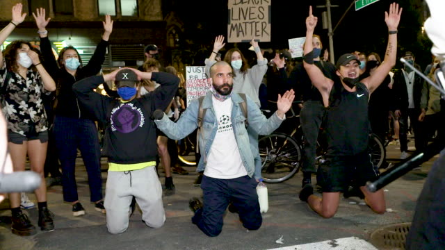 protestors kneel in front of new york city police officers in protest of the death of george floyd in minneapolis. throughout the march protestors... - ひざまずく点の映像素材/bロール