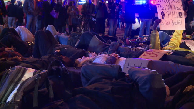 protestors lie in the street blocking traffic and chant against the grand jury decisions in the eric garner and mike brown cases - sprechgesang stock-videos und b-roll-filmmaterial