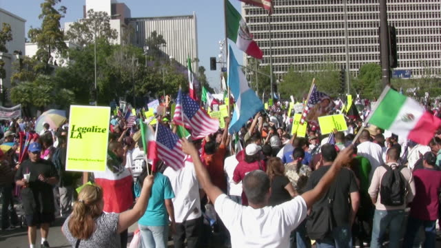protestors march in support of immigration reform during a may day rally for workers' rights in downtown - lavoratore emigrante video stock e b–roll