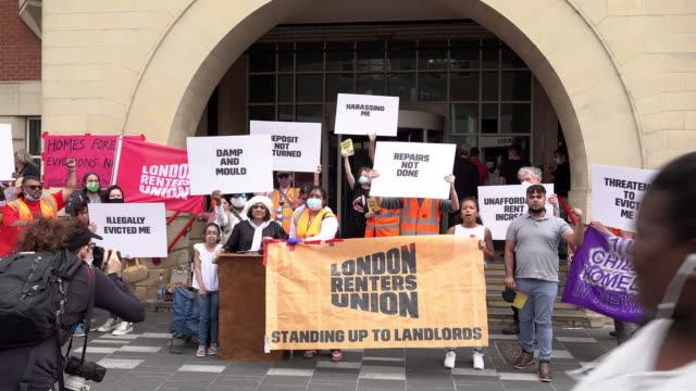 protestors on the london renters union day of action against evictions outside stratford magistrates court hold placards and chant slogans . - sign stock videos & royalty-free footage