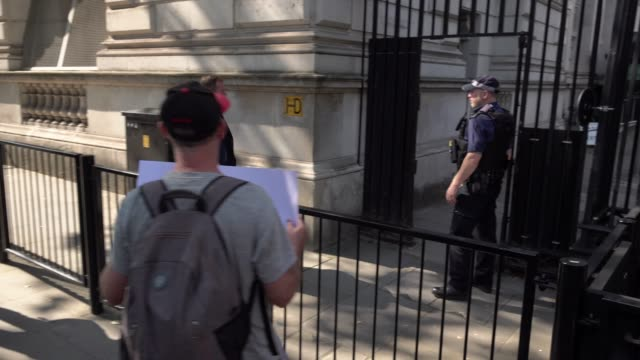 "protestors opposing the rule of six law block the gate to downing street in westminster and chant ""shame on you "" as a government worker enters on... - pianificazione di emergenza video stock e b–roll"