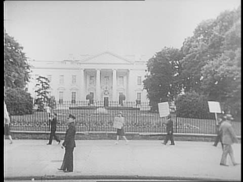 protestors picket with signs and american flags outside the white house asking for peace / signs read 'keep the light of peace burning' and 'no... - 1941年点の映像素材/bロール