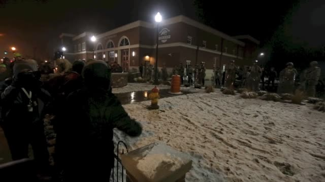 Protestors shout against annex security team members standing guard outside Ferguson Police Department during the ongoing protests after the Grand...