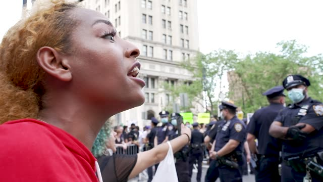 protestors stand behind steel barricades facing nypd in the midst of the coronavirus disease pandemic demonstrators rally at foley square in downtown... - anti racism stock videos & royalty-free footage