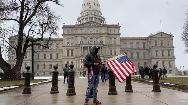 protestors stand outside the michigan state capitol which is protected by the national guard in lansing, mi, u.s., on sunday, jan. 17, 2021. a... - michigan stock videos & royalty-free footage