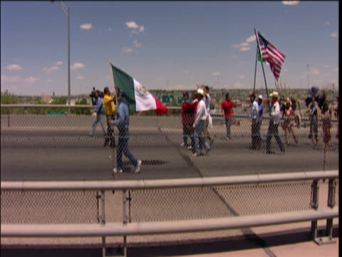 vídeos de stock, filmes e b-roll de protestors walking across bridge el paso texas usa - fronteira internacional