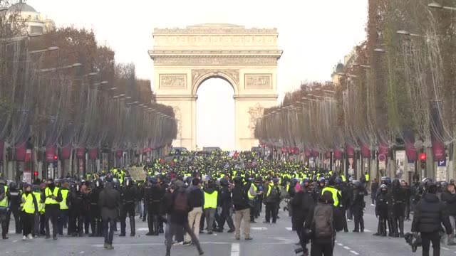 protestors wearing 'yellow vests' walk on the champs elysees avenue in paris on december 08, 2018 during a protest against rising costs of living... - demonstrant stock-videos und b-roll-filmmaterial