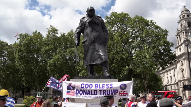 """protestors well known for supporting brexit protests unveil a banner underneath the winston churchill statue that says """"god bless donald trump two... - grooming stock videos & royalty-free footage"""