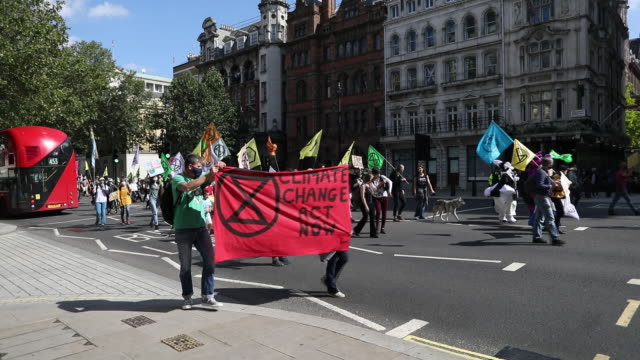 protestors with flags and banners marching through the street during a climate change protest organized by extinction rebellion near parliament... - english language stock videos & royalty-free footage