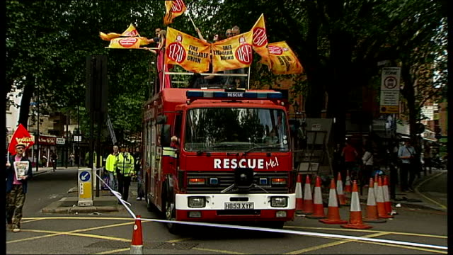 Protests against proposed London fire station closures ENGLAND London Clerkenwell EXT Protest march along led by fire engine playing song 'Burning...
