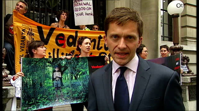 protests against vedanta mining company england london ext antimine protesters with banner outside vedanta agm building reporter to camera gv... - oeec video stock e b–roll