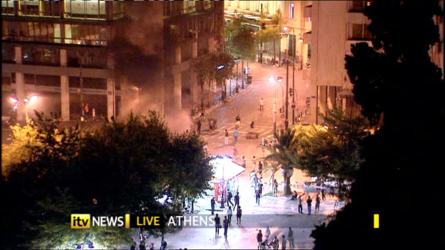 protests and general strike against government austerity measures greece athens high angle live shot demonstrators throwing missiles at riot police - ユーロ圏債務危機点の映像素材/bロール