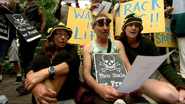 protests continue at west sussex fracking site **musioc heard sot** protesters sitting on ground and singing 'no more dirty energy' banner attached... - itv weekend lunchtime news点の映像素材/bロール