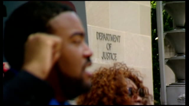 Protests follow George Zimmerman acquittal of Trayvon Martin shooting USA Washington Department of Justice EXT Low Angle shot of protesters one with...