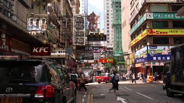 protruding chinese signs hang above a street in the mong kok district of hong kong china on monday sept 12 red taxis drive past as pedestrians cross... - mong kok stock videos and b-roll footage