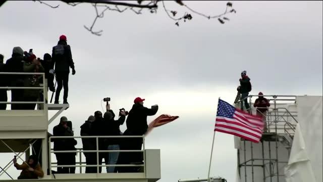 vídeos de stock e filmes b-roll de pro-trump protesters storm us capitol building; usa: washington dc: us capitol building: ext pro-trump protesters climbing up concrete wall onto... - capitólio capitol hill