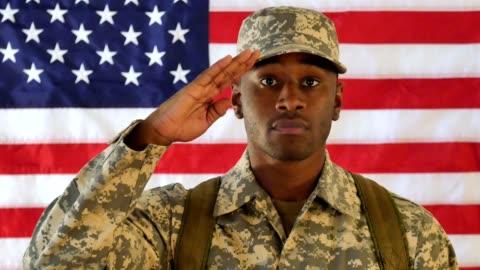 stockvideo's en b-roll-footage met trots op amerikaanse soldaat salutes terwijl staan voor de amerikaanse vlag - salueren