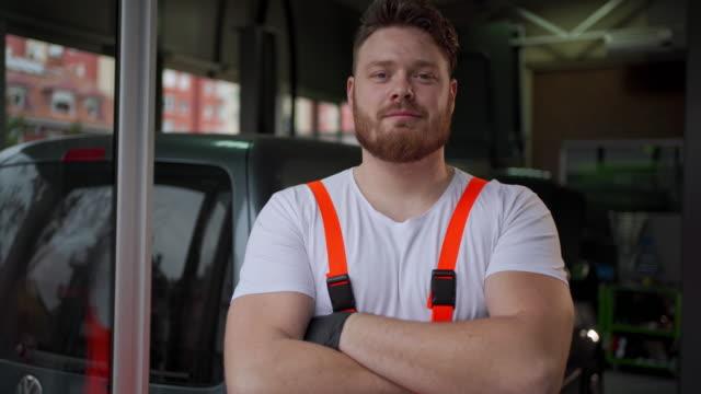 vídeos y material grabado en eventos de stock de orgulloso y guapo mecánico que trabaja en un taller de reparación de automóviles - mecánico de coches