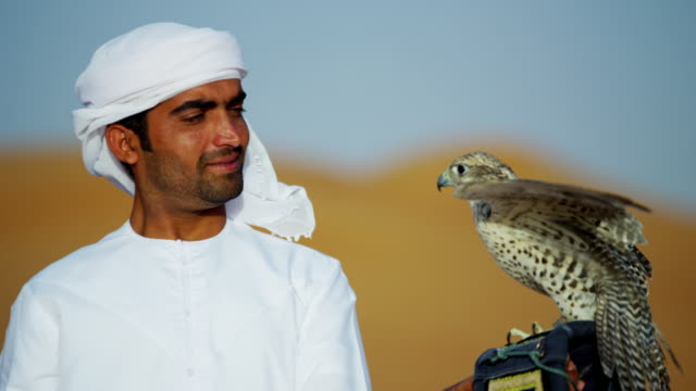 Proud Arab wearing dishdasha with his trained falcon