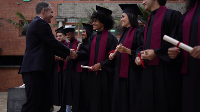 proud college headmaster handshaking all new graduates during their graduation ceremony while they smile - head teacher stock videos & royalty-free footage