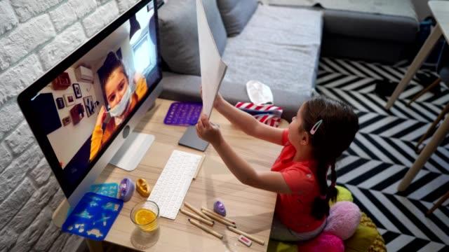 vídeos de stock, filmes e b-roll de orgulhosa menina bonita mostrando seu desenho para sua melhor amiga durante a chamada de vídeo - sentir a falta emoção