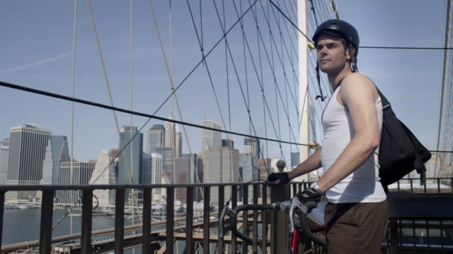 proud cyclist checks out the view on brooklyn bridge - solo uomini giovani video stock e b–roll