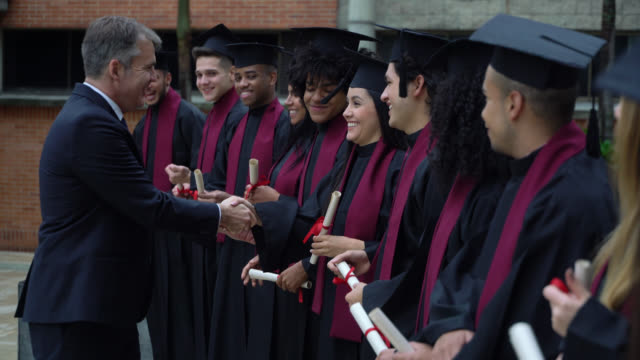 proud dean of the university handshaking each of the graduates while they hold their diplomas - head teacher stock videos & royalty-free footage