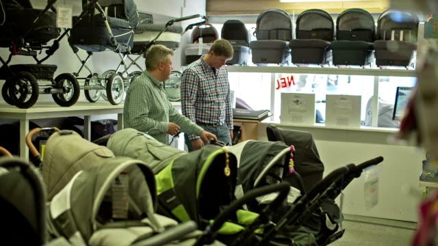 vídeos y material grabado en eventos de stock de a proud expectant father is looking for baby products - cochecito de bebé