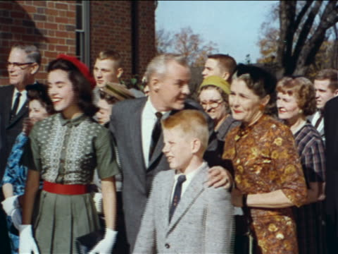 1962 proud family smiling + waving at graduation procession / industrial - family waving stock videos & royalty-free footage