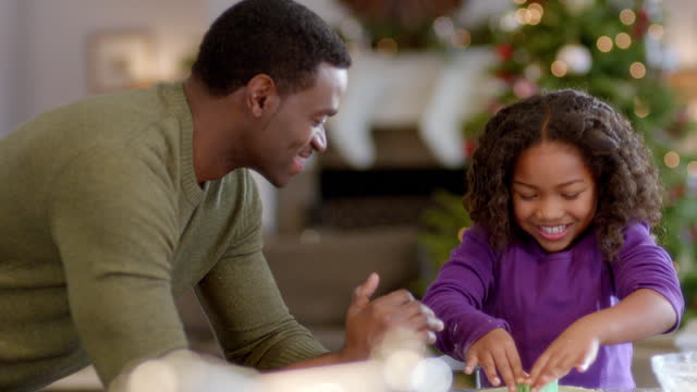 proud father watches daughter press christmas cookie-cutter shapes into cookie-dough (dolly-shot) - moulding trim stock videos & royalty-free footage
