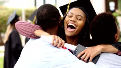stolta kvinnliga college examen ger föräldrarna en stor kram - examen bildbanksvideor och videomaterial från bakom kulisserna