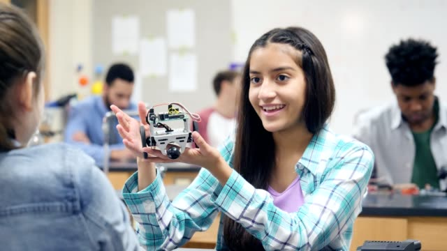 Proud female high school student shows off robot she made in class