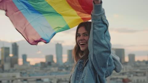lgbt orgoglioso. donna felice che tiene la bandiera lgbt. vista sul tetto - diritti lgbtqi video stock e b–roll