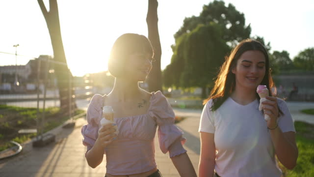 proud joyful lesbian couple holding hands and enjoying a ice cream during hot summer day - belly button piercing stock videos & royalty-free footage