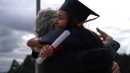 Proud MBA graduate hugging her dad celebrating after graduation ceremony