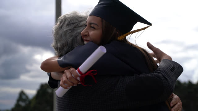proud mba graduate hugging her dad celebrating after graduation ceremony - etnia latino americana video stock e b–roll