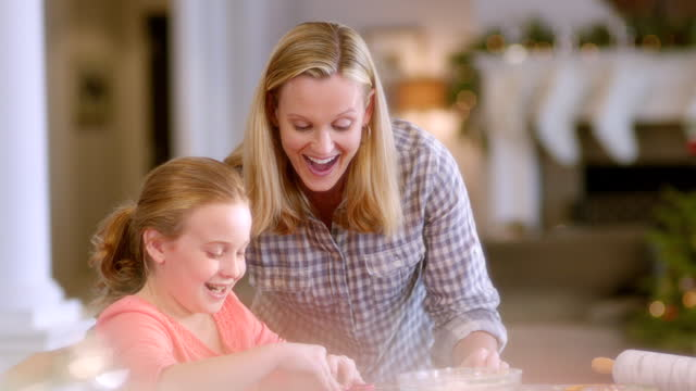 proud mother helps daughter press christmas cookie-cutter shapes into cookie-dough (dolly-shot) - christmas decoration stock videos and b-roll footage