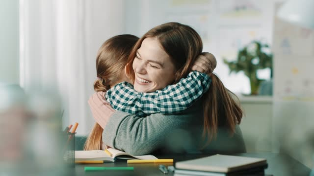 proud mother hugging daughter - homework stock videos & royalty-free footage