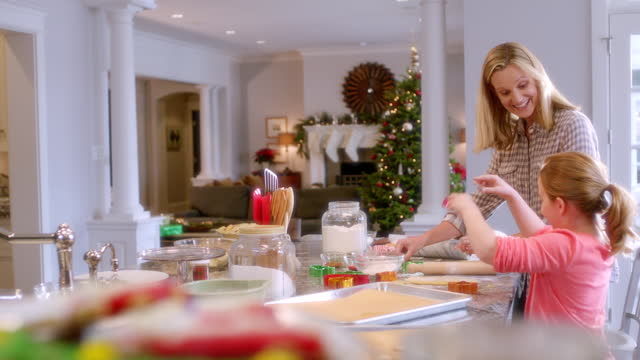 Proud mother watches daughter press Christmas cookie-cutter shapes into cookie-dough (dolly-shot)
