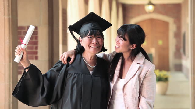Proud senior woman in cap and gown holding diploma and hugging daughter on graduation day