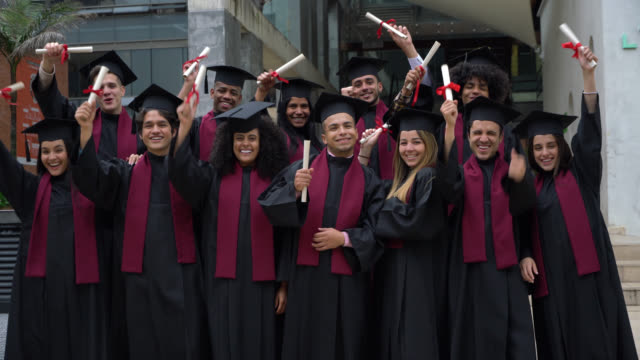 proud successful group of university graduates holding their diploma with their arms outstretched looking at camera smiling - graduation stock videos & royalty-free footage